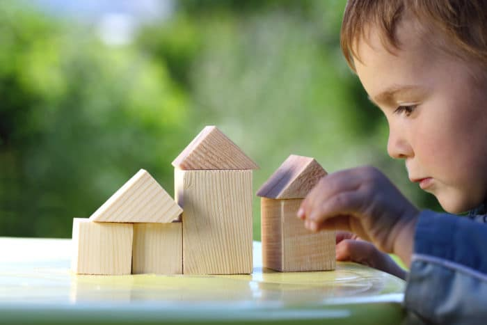 boy raises his hand to the house from wooden cubes