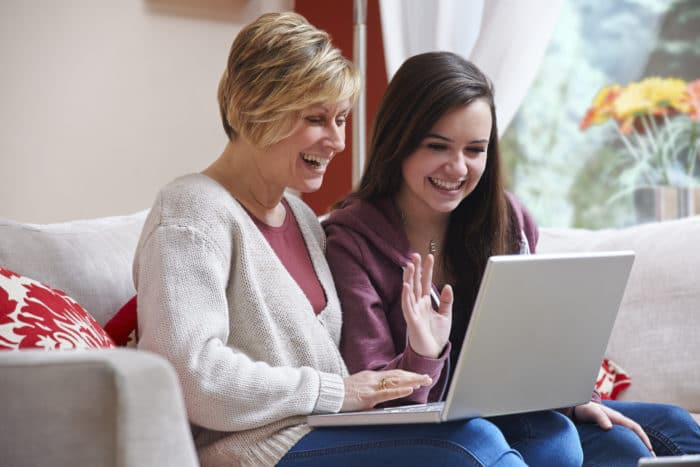 Mother and daughter smiling at laptop while using webcam