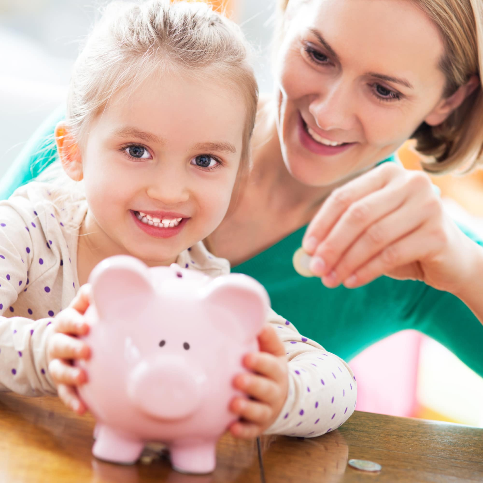 young girl and mom with piggy bank